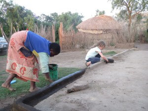 She then helped the older girl smear dung mixed with dirt and water onto the front patio of the boma.